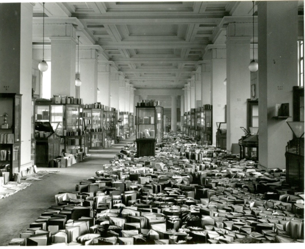 Black and white photo of books drying in Room 33 following a fire caused by the Blitz in 1941. The water used to put out the fire caused serious water damage to the Museum's library collection.