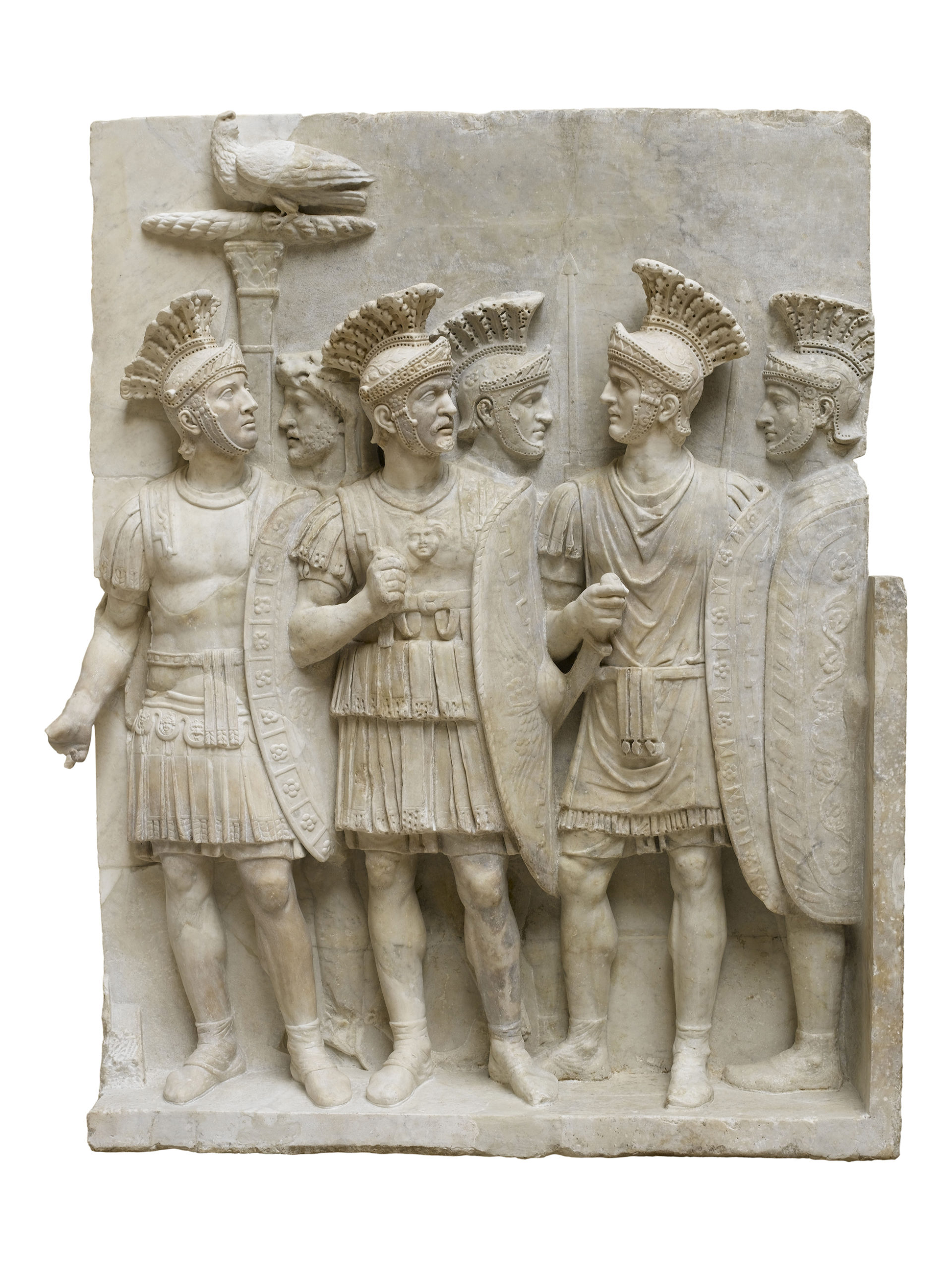 A cream coloured relief showing a group of 6 members of the praetorian guard in armour holding shields.