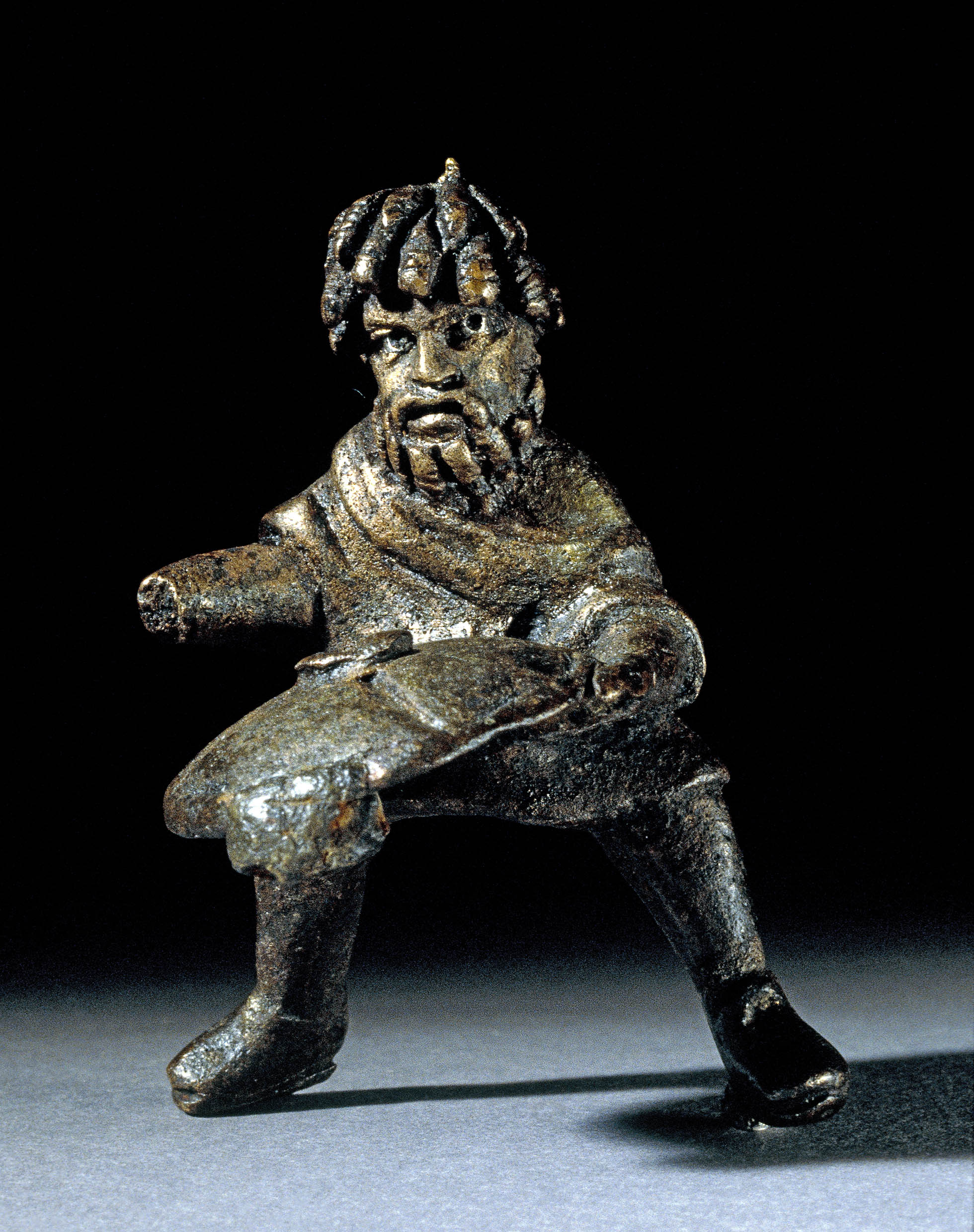 Small metal figure of a man with dreadlocks in a dynamic stance.