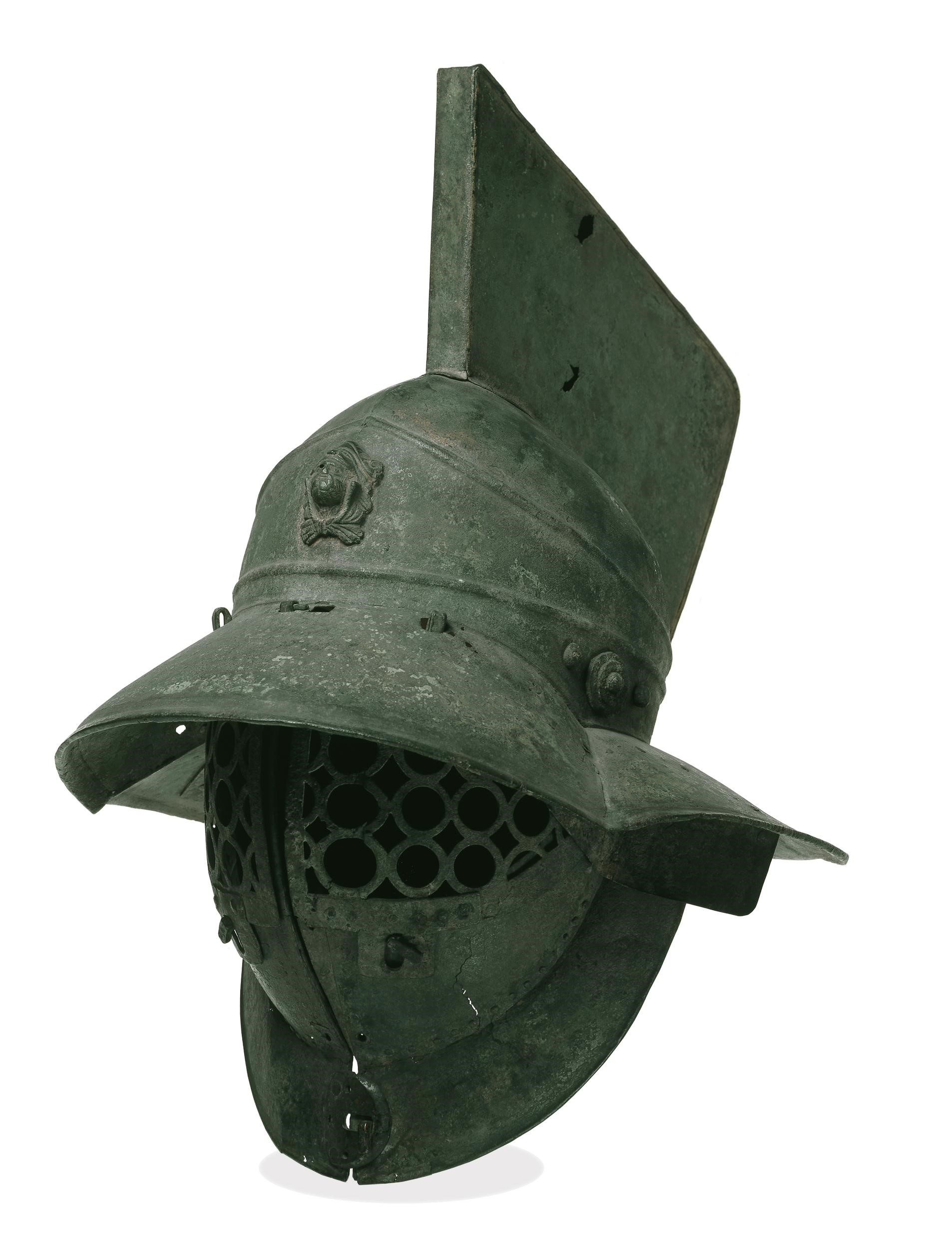 Bronze helmet with a grille of linked circles to protect the face, and a broad brim to protect the back and sides of the head. At the front of the helmet is a medallion of Hercules.