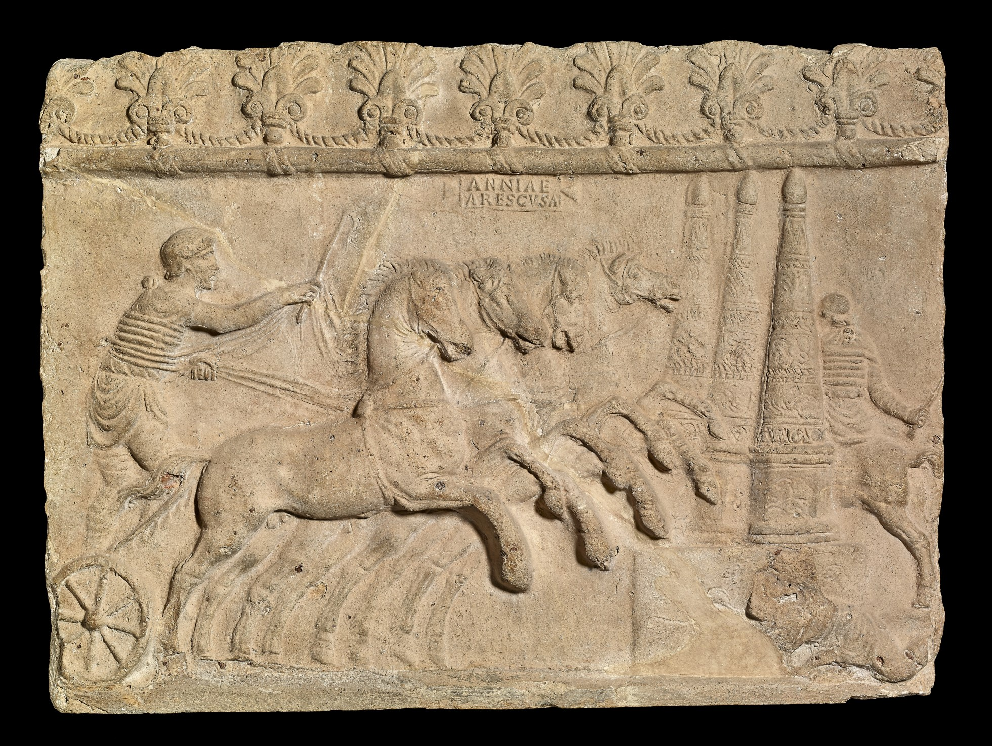 A cream coloured terracotta relief showing a chariot-race. A four-horsed chariot approaches the three columns of the turning-post. The charioteer wears a cap, leggings, and a short tunic with fasciae (protective leather straps). The reins are passed tightly around his waist. A jubilator, a rider who encourages the contestants, has already turned. A charioteer, fallen from his chariot, crouches at the base of the turning-post.