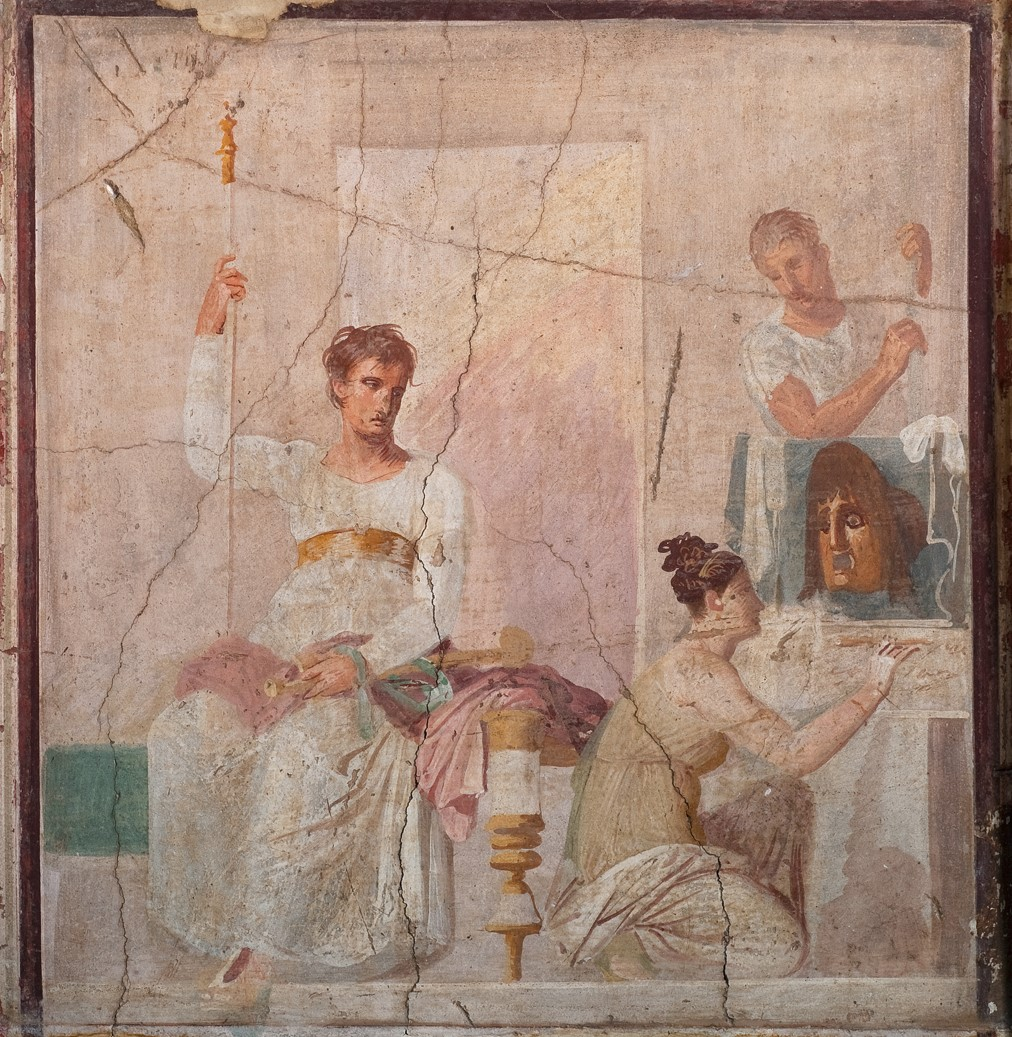 Painting showing a man seated to the left wearing a white long sleeved tunic and holding a staff. He looks towards a woman on the right who  crouches and looks at a painting of a theatrical mask. A man stands behind the painting.