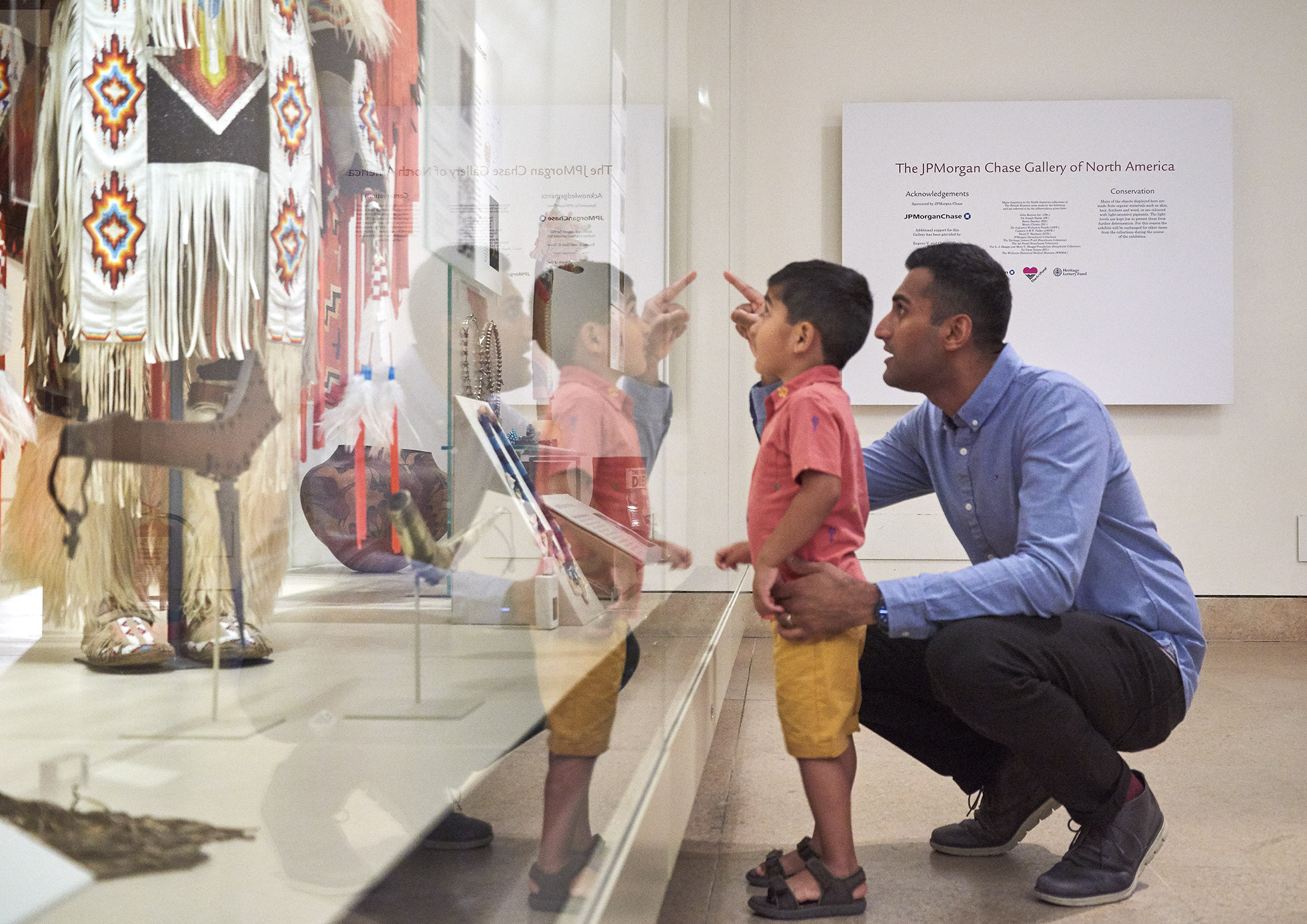 A father and son stand in front of a display case, looking at one of the objects inside.