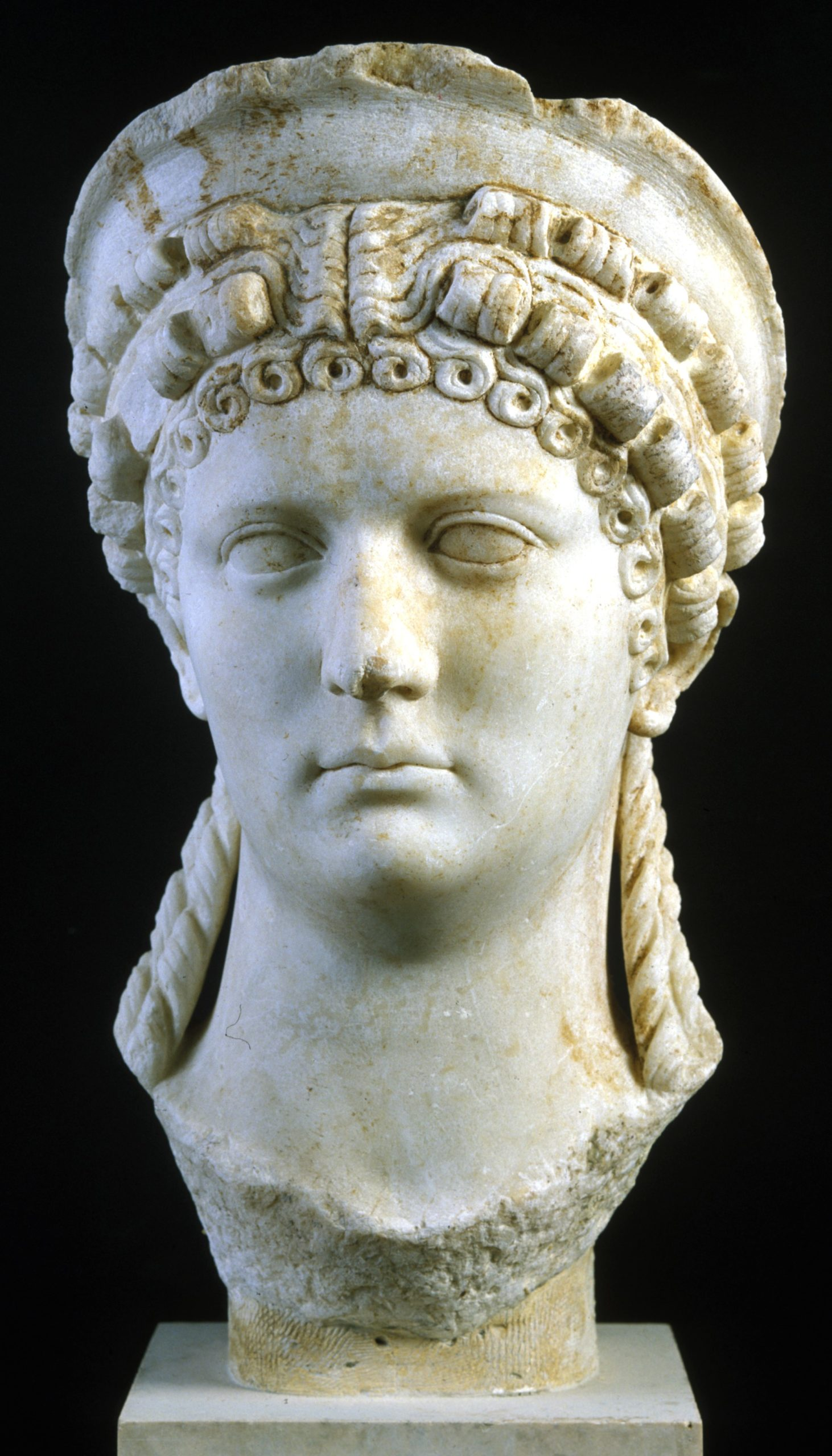 Bust of a woman in cream marble. She has an elaborate hairstyle, including curls on her forehead and ringlets falling from the back of her head to her shoulders.