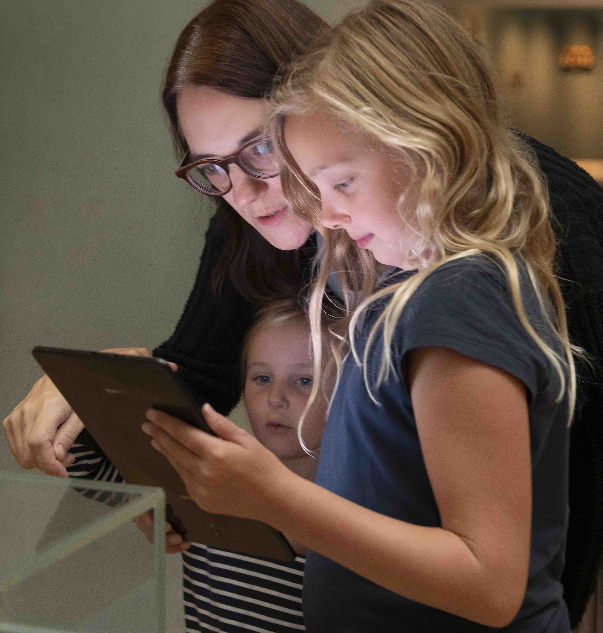 A mother and two daughters gather around a tablet device in one of the galleries.