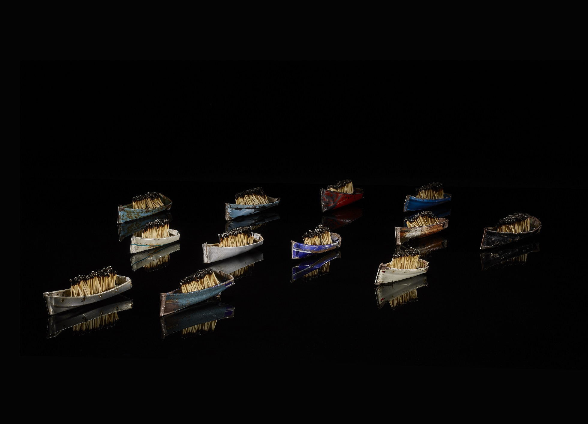 12 miniature boats made from recycled bicycle mudguards, extinguished matches and clear resin are displayed in a flotilla on a black background which reflects the boats as though it was water.