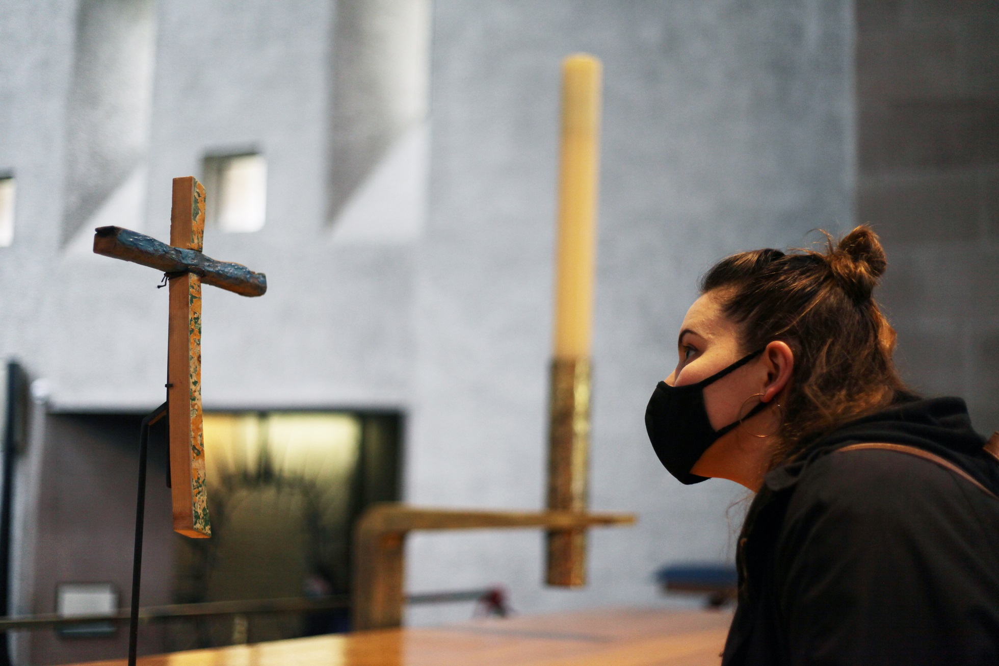 A young woman with a mask looks at the Lampedusa cross on display on the high altar in Coventry Cathedral.