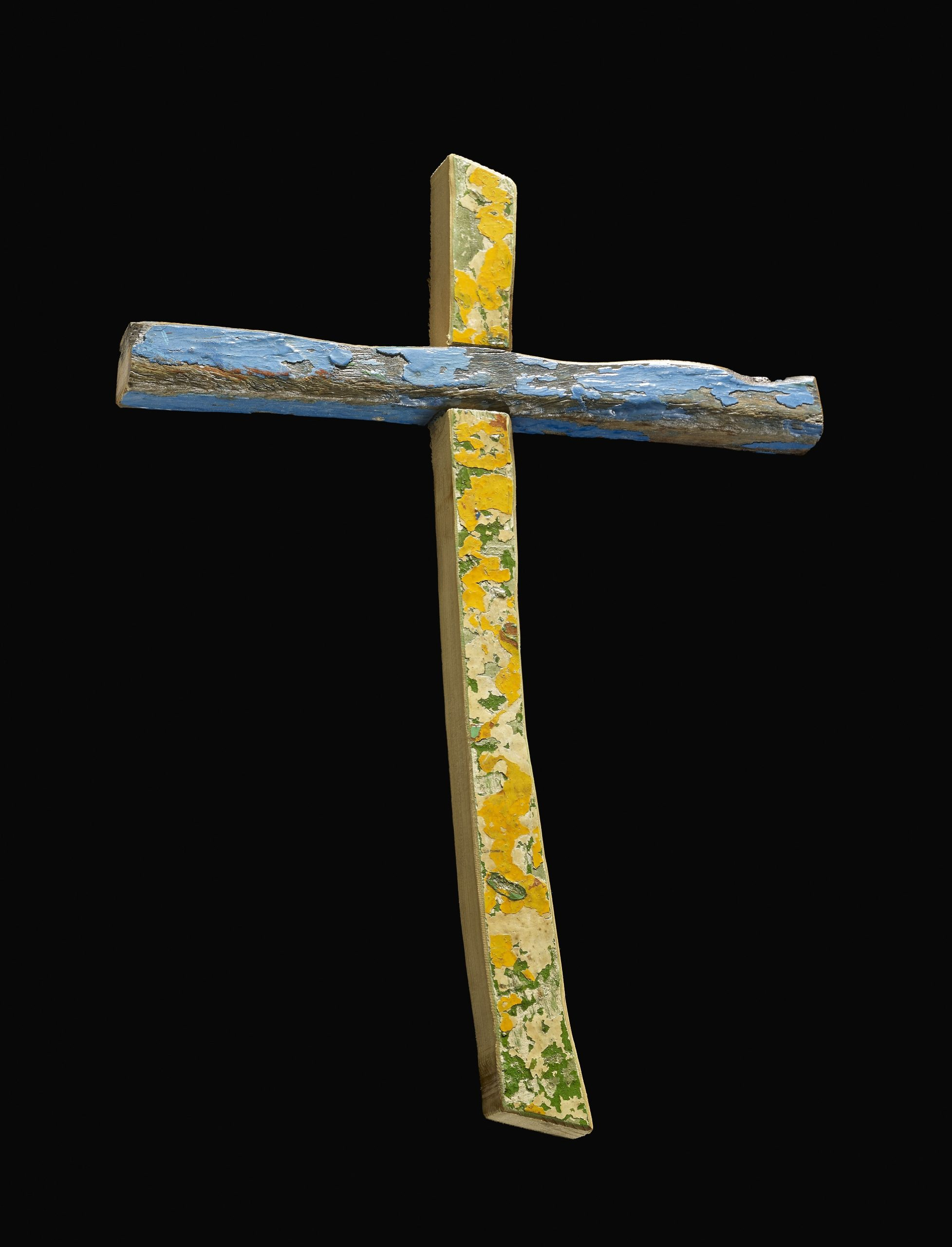 Wooden cross made from pieces of a boat. The vertical piece is yellow and green and the horizontal piece is blue.  The vertical and horiziontal pieces are joined with a cross halved joint. The cross piece retains scuffed blue paint on the front, upper and lower surfaces. The front of the vertical section has layers of damaged paint.